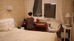 Woman in leopard print dress playing piano in bedroom window. Stock Footage