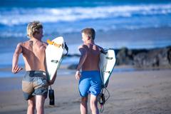 Two teenage male surfers running toward sea, Fuerteventura, Spain - stock photo