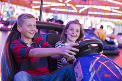 Brother and sister on fairground bumper cars Stock Photos