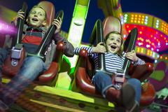 Sister and brother on fairground ride at night - stock photo