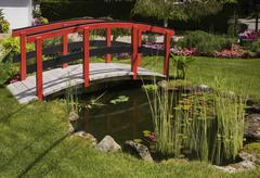 Red and black footbridge over pond with  in landscaped garden, Quebec, Canada Stock Photos