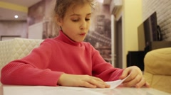 Girl at table reading aloud text in English with paper. Stock Footage