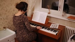 Woman with headphones sitting near window and piano playing. Stock Footage