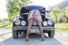 Mature woman bent over car, looking in bonnet - stock photo