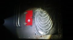 Flashlight beam moving along metal panel with cables in dark. Stock Footage