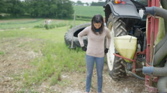 4K Portrait of smiling female farmer standing next to tractor Stock Footage