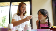 Slow motion of Asian mother feeding sushi for her daughter in a restaurant - stock footage