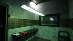 Interrogation room with mirror, table, benches and swinging lamp. Stock Footage