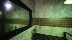 Swinging lamp in horrible dark room with mirror, bench and door. Stock Footage