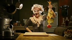 Funny senior housewife is cooking chicken in an old kitchen - stock footage
