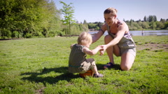 Mother playing with daughter in park Stock Footage