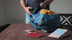 Man puts things in a backpack Stock Footage