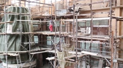 Scaffolding around lower sculpture of konung Vladimir and people on it Stock Footage