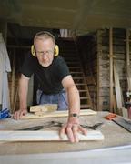 Senior man doing carpentry in workshop - stock photo