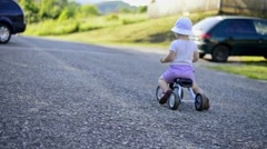 Litle girl riding a bicycle outside in sunny nature Stock Footage