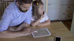 Father and daughter, playing on tablet, sitting in kitchen Stock Footage