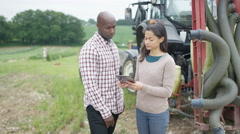 4K Portrait smiling farming couple standing next to tractor with computer tablet Stock Footage
