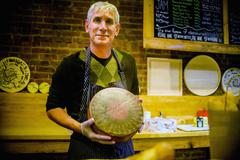 Portrait of an artisan cheese maker in a cheese shop. Stock Photos