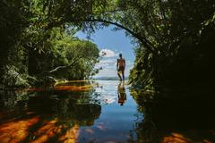 Man wearing swimming trunks, standing under a tree by a river. Stock Photos