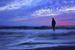Man standing in ocean waves at sunset, cloudy sky. Kuvituskuvat