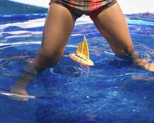 A child playing with a model sail boat in water, legs astride. Stock Photos