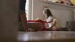 Father and daughter, playing with toys, sitting on floor Stock Footage