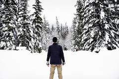 Rear view of a man standing in the snow in a forest in winter. Stock Photos