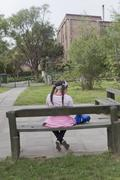 Young girl sitting on bench, rear view - stock photo
