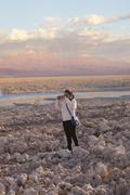 Young girl taking photograph of arid landscape of Salar de Atacama, San Pedro, Stock Photos