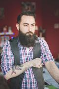 Young bearded man folding shirt sleeve - stock photo