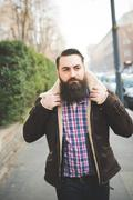Young bearded man on pavement - stock photo