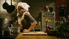 Funny senior housewife is cooking in an old kitchen - stock footage