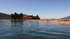People walking along The Floating Piers work of art. View of St. Paul Island Stock Footage