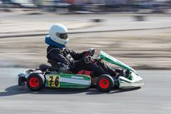 Karting - driver in helmet on kart circuit - stock photo