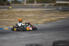 Karting - driver in helmet on kart circuit Stock Photos