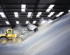 Digger loading bulk fertilizer in port Stock Photos