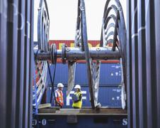 Female and male workers inspecting shipping containers in port, Grimsby, - stock photo