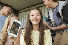 Girl holding up smartphone selfie of friends in shelter - stock photo