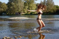 Young woman wearing a bikini splashing and playing in river Stock Photos