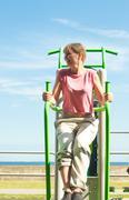 Active woman exercising on leg raise outdoor. Stock Photos