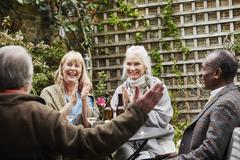 Senior friends sitting in garden talking Stock Photos