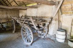 Old wooden cart inside barn - stock photo