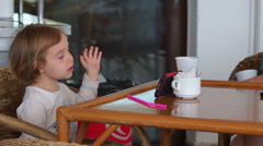 Little girl seating in the outdoor cafe, biting mosquito and using smartphone. Stock Footage