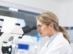 Scientist viewing sample on glass slide through microscope for medical testing - stock photo