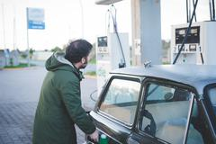 Man using fuel pump for vintage car in gas filling station - stock photo