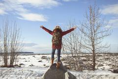Woman standing on rock with arms out, Anchorage, Alaska - stock photo