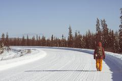 Person walking on snow covered road, Fairbanks, Alaska - stock photo