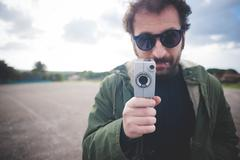 Portrait of mid adult man posing with vintage movie camera on waste ground - stock photo