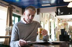 Mature man drinking beer and reading newspaper in pub - stock photo