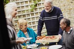 Senior man serving friends pizza in garden - stock photo